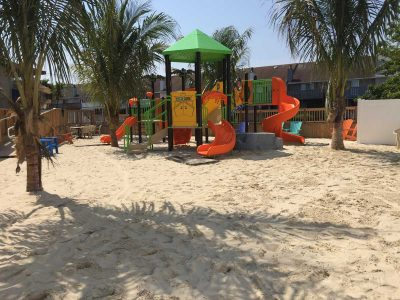 A green, yellow and orange playset in white sand with palm trees at the Parched Pelican at Ocean City Maryland