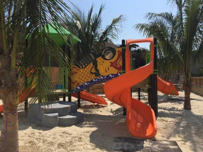 A green, orange and yellow playset with slides, steps and a fish bridge at the Parched Pelican at Ocean City Maryland