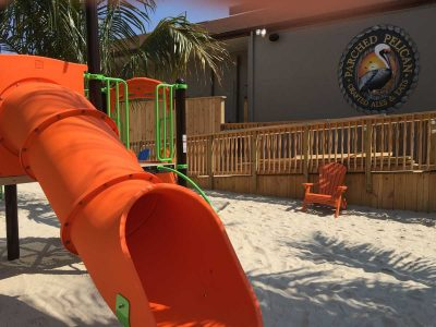 A green, orange and yellow playset with orange chair, wheelchair ramp and Parched Pelican logo at the Parched Pelican at Ocean City Maryland