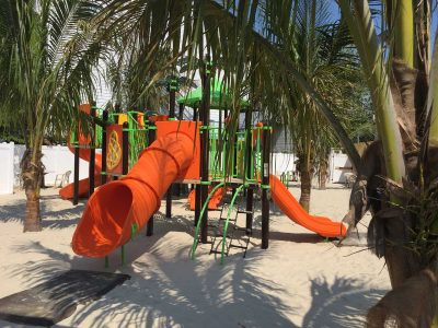 Peering through palm trees at a green, orange and yellow playset in white sand at the Parched Pelican at Ocean City Maryland