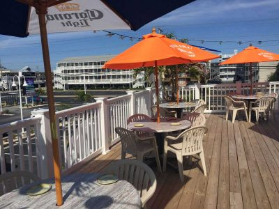 An outdoor dining area and deck with orange and blue umbrellas inside circular tables overlooking the parking lot and highway at the Parched Pelican at Ocean City Maryland